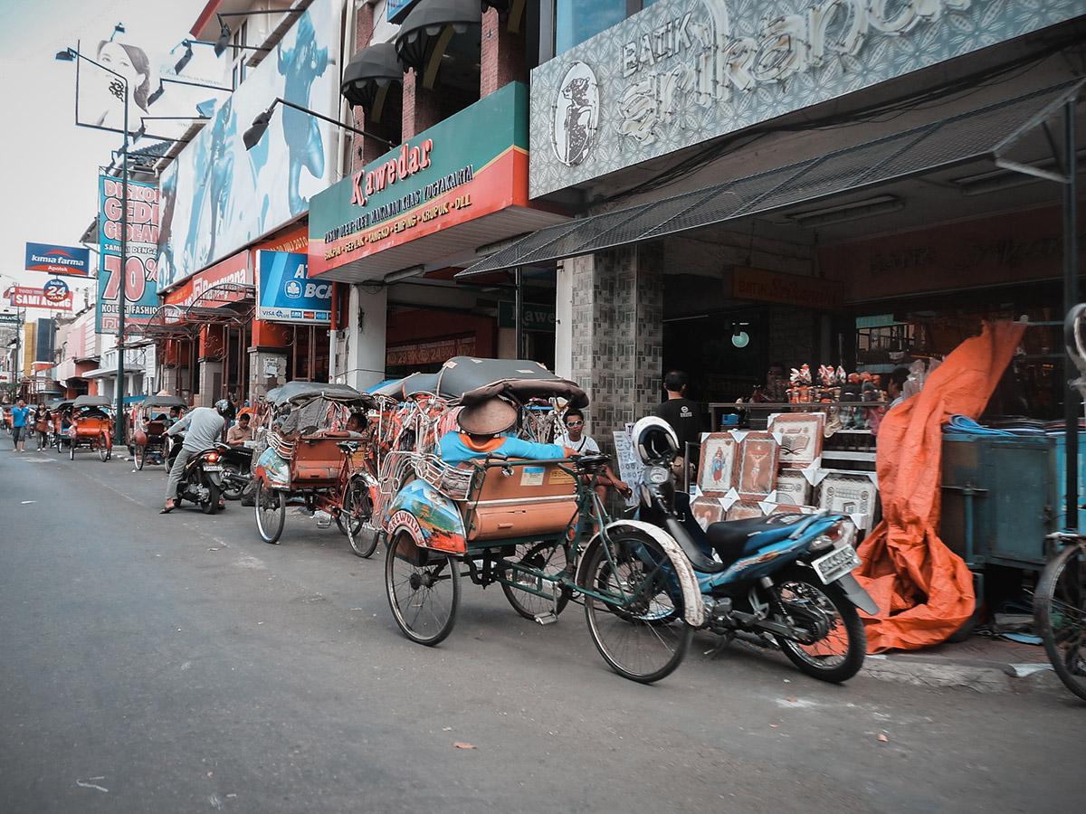 I classici becak parcheggiati fra i negozi