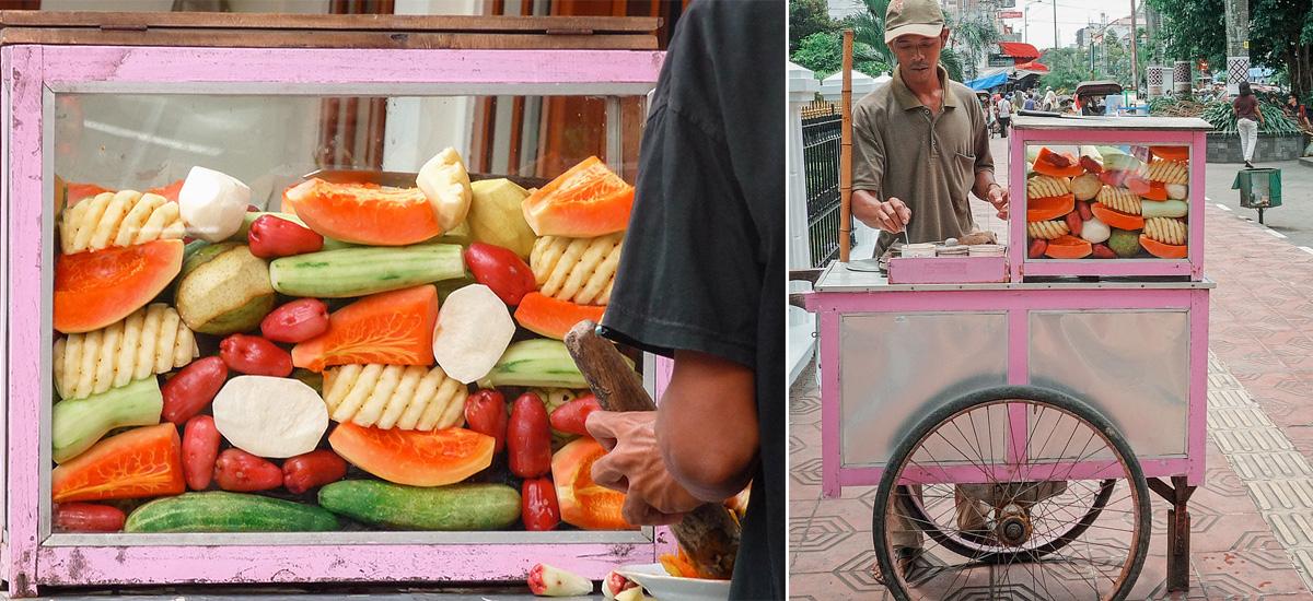 Un venditore che prepara il rujak: una macedonia con arachidi e sambal