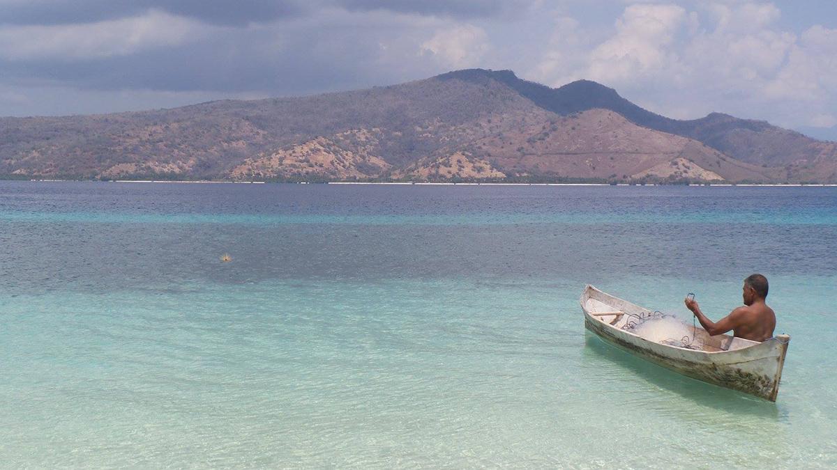 Flores e il Parco di Komodo Uomo in barca su un mare cristallino dell'isola di Flores