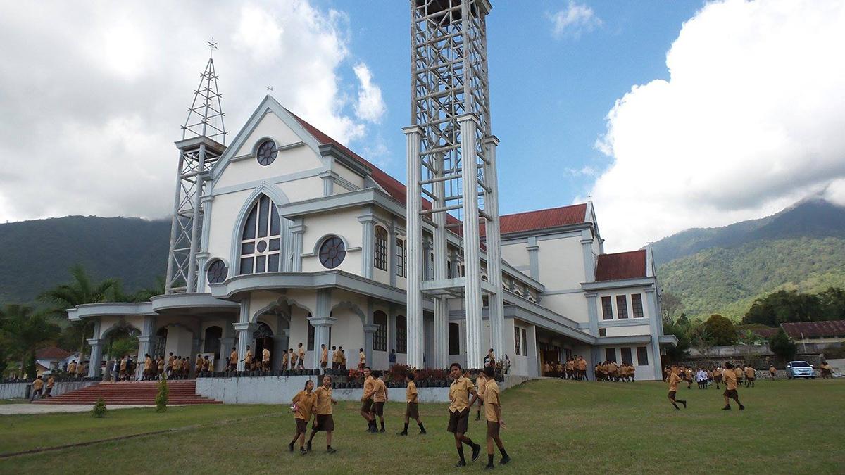 Flores e il Parco di Komodo, la chiesa cattolica di Ruteng con dei ragazzi che giocano nel prato