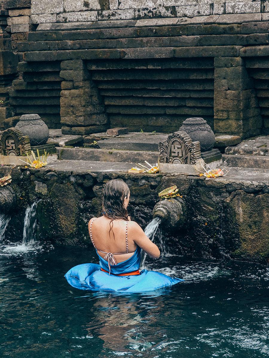 Una donna si purifica sotto un beccuccio delle sorgenti di Tirta Empul