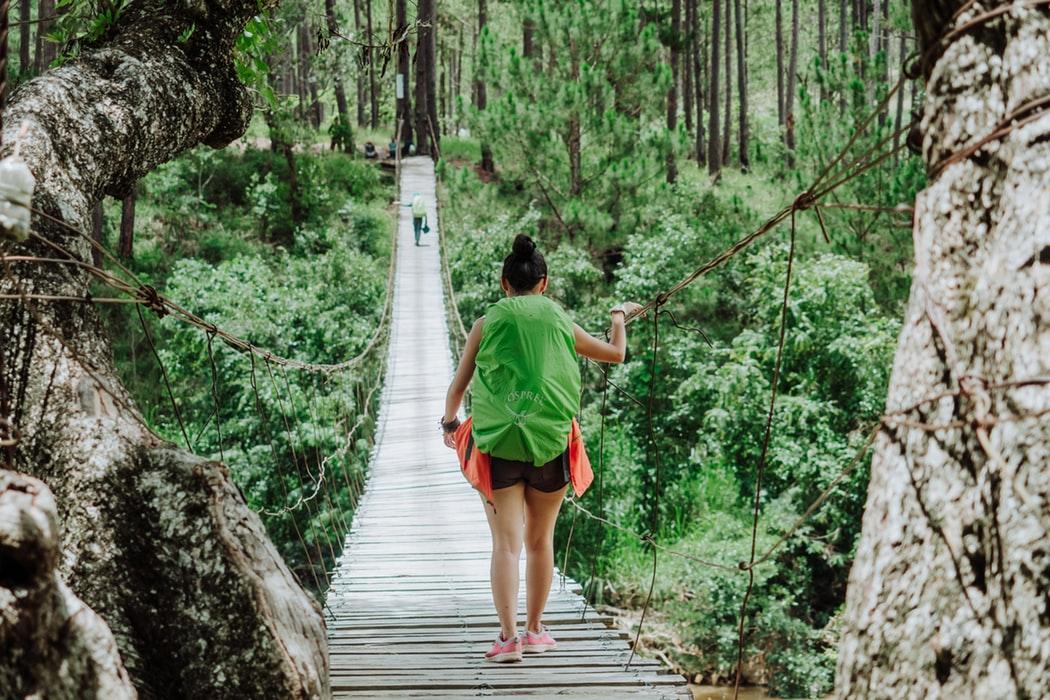 Scegliere la migliore assicurazione di viaggio. Ragazza attraversa un ponte sospeso nella giungla.