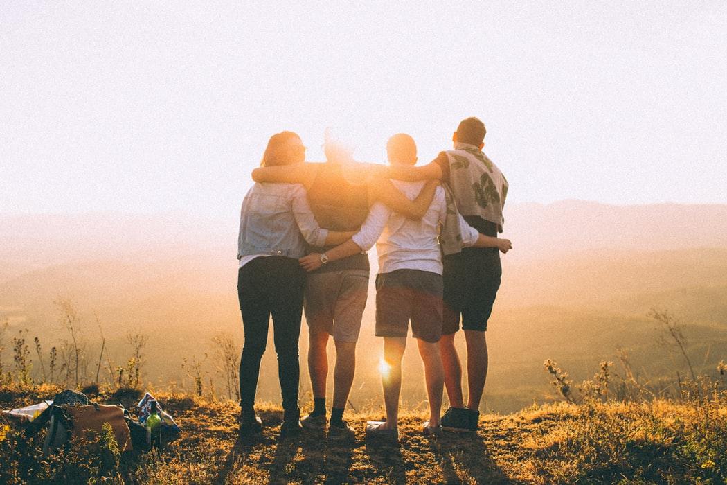 Scegliere la migliore assicurazione di viaggio. Amici che si abbracciano.