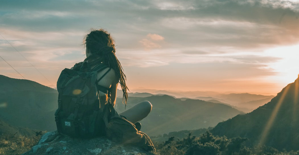 Scegliere la migliore assicurazione di viaggio. Una ragazza riposa in cima a un monte.